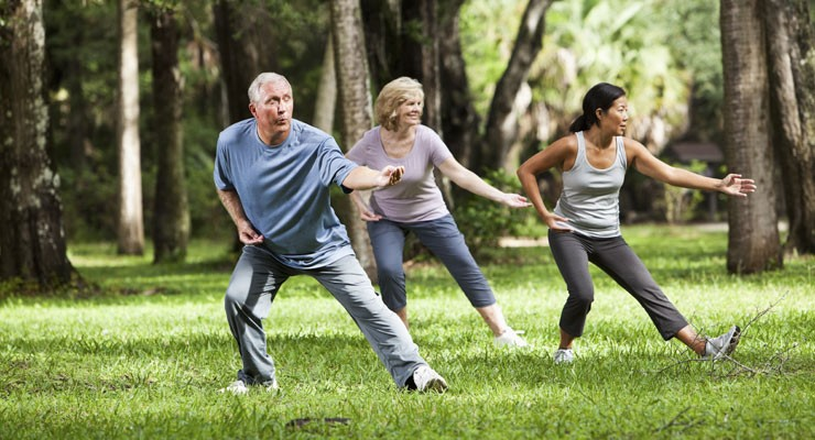 man and two women doing tai chi in a park