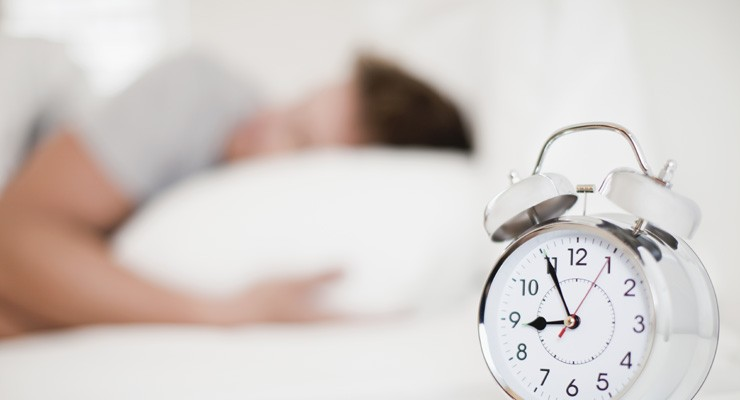 man sleeping with alarm clock in the foreground