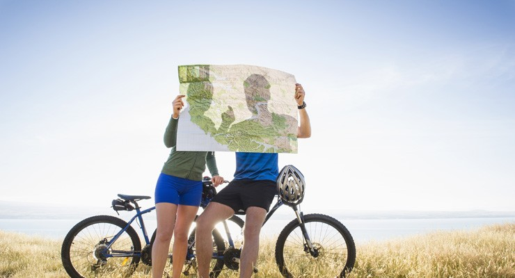 two people with bicycles looking at a map
