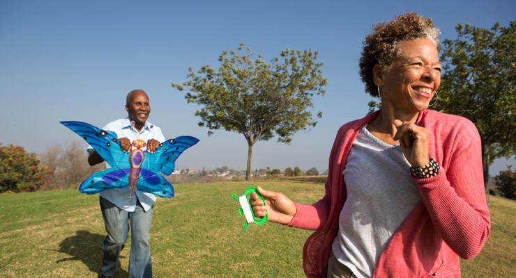 man and woman in field flying a kite