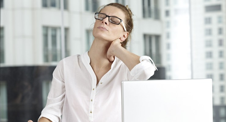 woman in front of laptop rubbing her neck