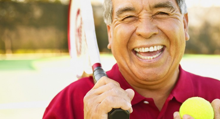man smiling holding a tennis racket and tennis ball