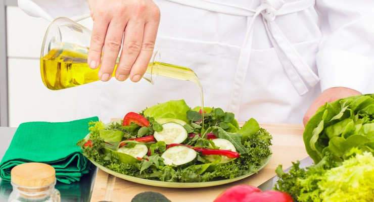 person pouring olive oil on plate of salad