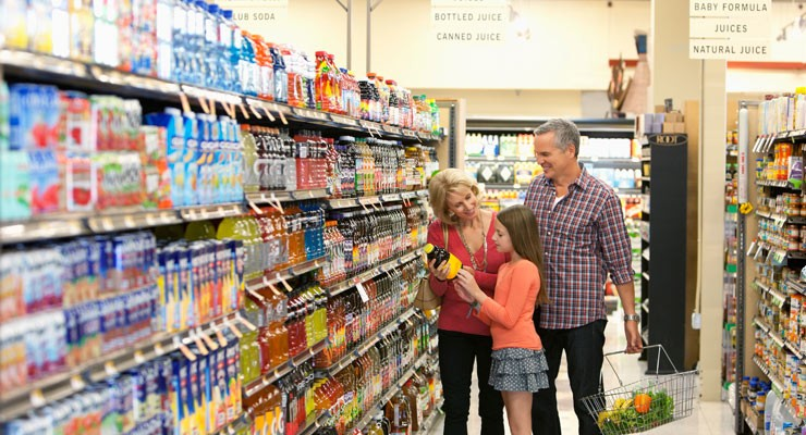 man, woman and small girl in grocery store aisle