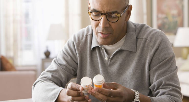 man reviewing two medication bottles