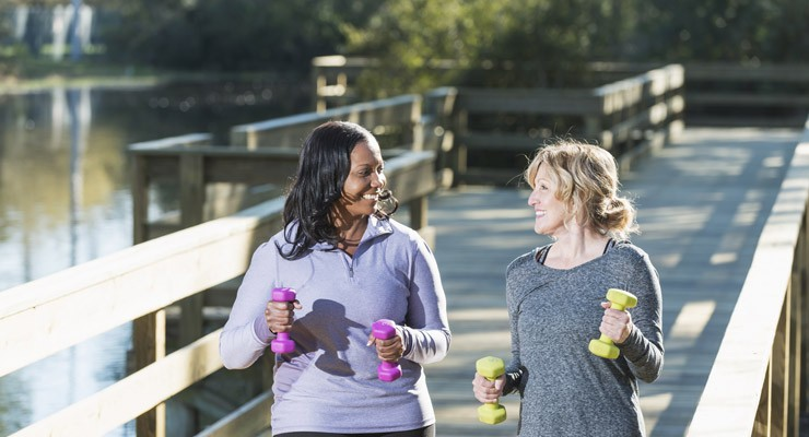 two women walkng on a foot bridge with hand weights