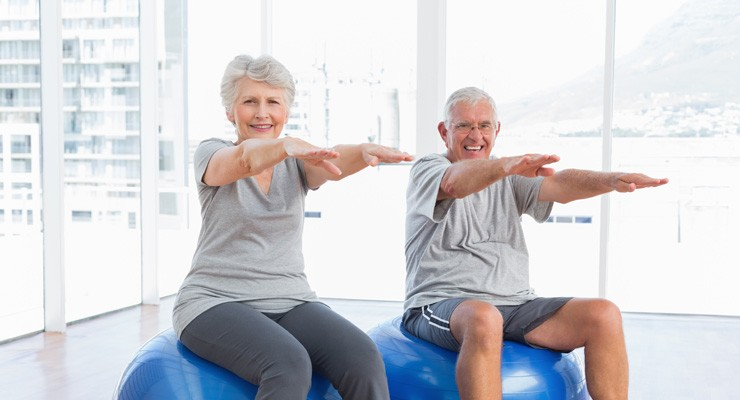 older man and woman sitting on exercise balls