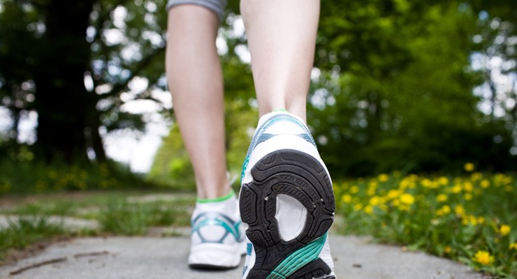 image of woman's lower legs in sneakers, walking away